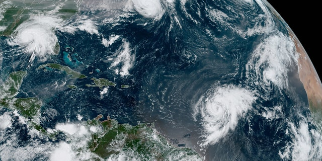 Hurricane Sally swirls near the Gulf Coast (top left) as Hurricane Paulette moves away from Bermuda and other systems swirl in the Atlantic Ocean on Sept. 15, 2020.