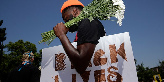 FILE - In this July 20, 2020, file photo, holding flowers and a sign, Blair Toles, 30, attends rally in Los Angeles, on Black Strike Day. Ahead of Labor Day, major U.S. labor unions say they are considering work stoppages in support of the Black Lives Matter movement. (AP Photo/Jae C. Hong, File)