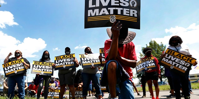 FILE - In this July 20, 2020, file photo, Eddie Perkins takes a knee during a protest rally outside Hartford Nursing & Rehabilitation Center in Detroit. Ahead of Labor Day, major U.S. labor unions say they are considering work stoppages in support of the Black Lives Matter movement. (AP Photo/Paul Sancya, File)