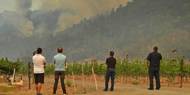People gather to watch as the Glass Fire burns above in the hills of Calistoga, Calif., on Monday, Sept. 28, 2020.