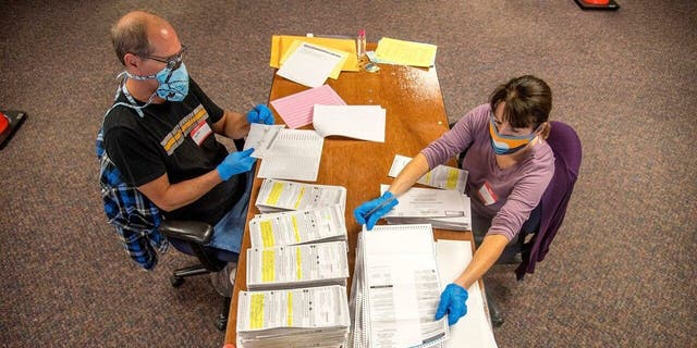 In this photo provided by Wisconsin Watch, election workers Jeff and Lori Lutzka, right, process absentee ballots at Milwaukee's central count facility on Aug. 11, 2020. Wisconsin elections officials are taking multiple steps to make mail-in voting smoother in November, when most people are expected to vote absentee. (Will Cioci/Wisconsin Watch via AP)