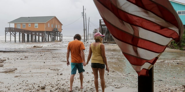 Adam Maubach, left, and Jo Dove look at the erosion caused by Tropical Storm Beta on Monday, Sept. 21, 2020, in Surfside, Texas.