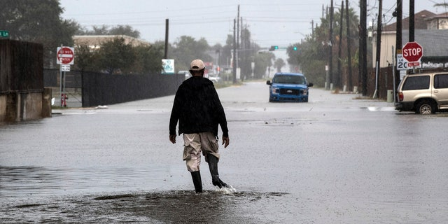 A man walks through a street flooded by Tropical Storm Beta Monday, Sept. 21, 2020, in Galveston, Texas.
