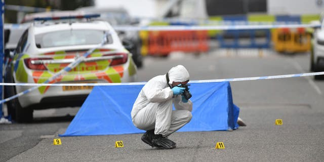 A police forensics officer taking photographs in Birmingham after several people were stabbed in the city center on Sunday. (AP/PA)