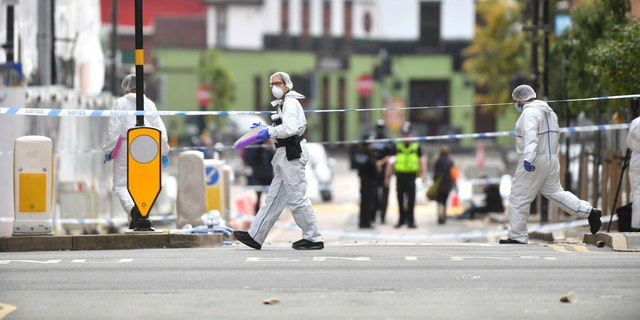 Police forensic officers investigate one of the stabbing scenes. (AP/PA)