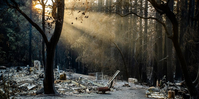 Sun rays are highlighted by smoke from the CZU Lighting Complex Fire as remains of a house sit on a parcel off Vick Drive near Empire Grade in Bonny Doon, Calif., on Thursday, Aug., 27, 2020.