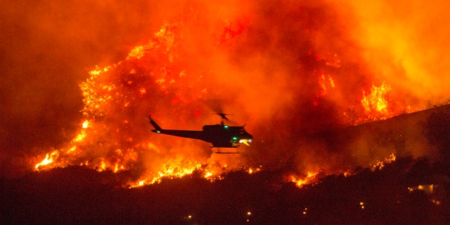 This Saturday, September 5, 2020, a helicopter prepares to drop water in a wildfire in Yucaipa, California.