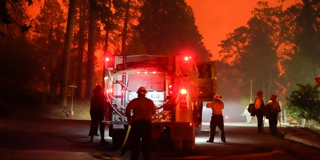 Firefighters perform near an Edison power plant in southern California to protect it from the advancing Creek fire in Big Creek, California on Sunday, September 6, 2020.