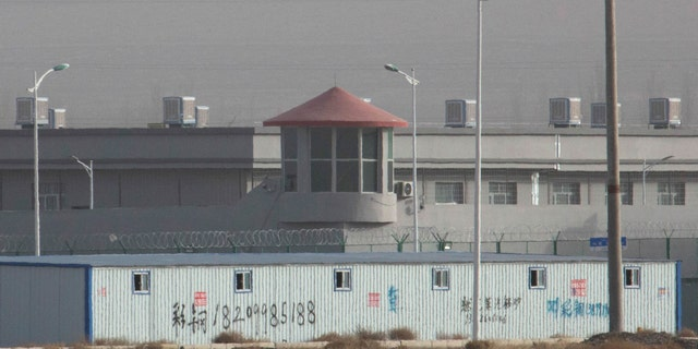 In this 2018 photo, a guard tower and barbed wire fences are seen around a facility in the Kunshan Industrial Park in Artux in western China's Xinjiang region. An Australian think tank says China appears to be expanding its network of secret detention centers in Xinjiang, where Muslim minorities are targeted in a forced assimilation campaign. (AP)