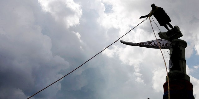 Venezuelan demonstrators use ropes to topple a Christopher Columbus statue in Caracas, October 12, 2004. REUTERS/Jorge Silva