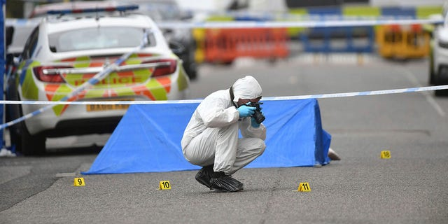 A police forensics officer taking photographs in Irving Street, in Birmingham after a number of people were stabbed in the city centre on Sunday. (Jacob King/PA via AP)
