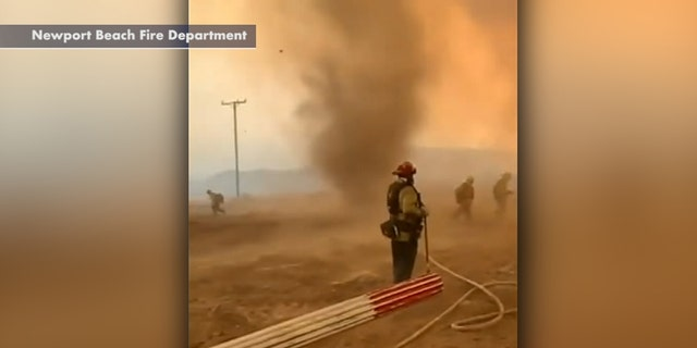 A smoke dust devil rages as firefighters battle the El Dorado wildfire in California.