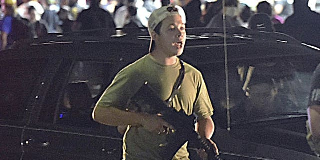 Aug. 25, 2020: Kyle Rittenhouse carries a weapon as he walks along Sheridan Road in Kenosha, Wis., during a night of unrest following the weekend police shooting of Jacob Blake. The way his lawyers tell it, the teenager wasn't a scared, gun enthusiast in over his head when he fatally shot two protesters. He was a courageous defender of liberty, a patriot exercising his right to bear arms amid chaos in the streets. But some legal experts say Rittenhouse's lawyers are taking big risks by turning a fairly straightforward self-defense case into a sweeping political argument that mirrors the law-and-order re-election campaign of President Donald Trump. (Adam Rogan/The Journal Times via AP)