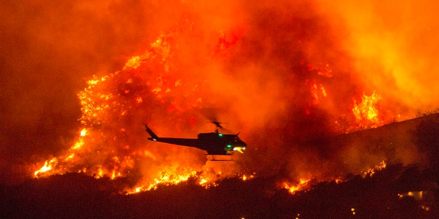 On this Saturday, September 5, 2020, file photo, a helicopter prepares to release water in a wildfire in Yucapea, California.