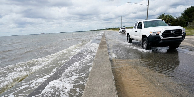 Waters from the Gulf of Mexico poor onto a local road, Monday, Sept. 14, 2020, in Waveland, Miss.