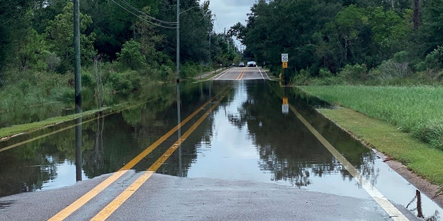 Waters begin to flood Davis Avenue from the Davis Avenue River in Pass Christian, Miss., Monday, Sept. 14, 2020, as rains associated with incoming Hurricane Sally begin to overflow its banks.