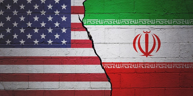 A cracked brick wall painted with an American flag on the left and an Iranian flag on the right.