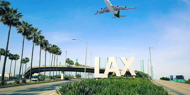A Los Angeles airport (LAX) sign is seen with a jet flying overhead.