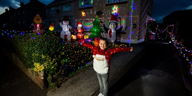 Theo Gabe, 5, outside of his home in Wales, which mom Caroline has decorated with 3,000 Christmas lights, sparkling snow and oversized, inflatable yuletide characters.