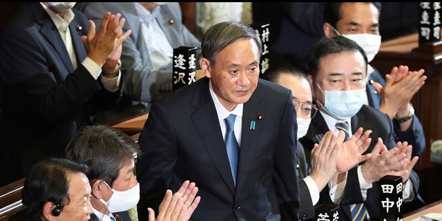Yoshihide Suga is applauded after being elected as Japan's prime minister at the parliament's lower house in Tokyo, Wednesday, Sept. 16, 2020. Suga was formally elected Wednesday as new prime minister in a parliamentary vote, replacing Shinzo Abe. (AP Photo/Koji Sasahara)