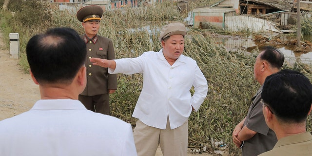 In this Saturday, Sept. 5, 2020, photo provided by the North Korean government, North Korea leader Kim Jong Un talks to officials as he visits a damaged area in the South Hamgyong province.