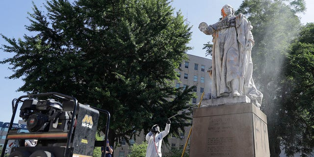 In this June 2, 2020 file photo, a worker cleans the King Louis XVI statue in Louisville, Ky., after it was hit with paintballs during a protest the previous evening. (AP Photo/Darron Cummings)