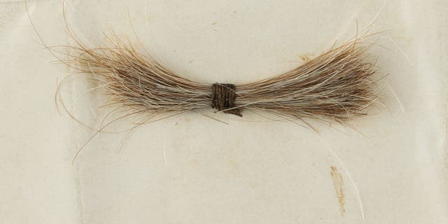 A lock of President Abraham Lincoln's hair attached to a bloodstained telegram sold for more than $81,000  at auction that ended Saturday.  (Credit: RR Auction)