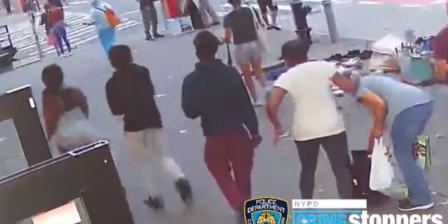 A 74-year-old woman (wearing a white shirt) confronts a group of teenagers after her purse was stolen before she was punched in the face on Thursday.