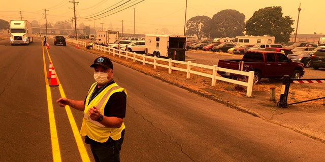 Under a smoke-filled sky, volunteer Shawn Daley directs traffic into the parking lot an evacuation center at the Oregon State Fairgrounds, which was crowded with hundreds of cars, pickup trucks, and campers of evacuees, in Salem on Tuesday, Sept. 8, 2020.