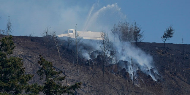A tanker truck sprays water on a persistent hotspot of a wildfire on a ridge, Wednesday, Sept. 9, 2020, near Bonney Lake, Wash., south of Seattle.