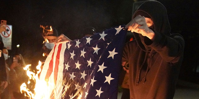A protester burns an American flag while rallying at the Mark O. Hatfield United States Courthouse on Saturday, Sept. 26, 2020, in Portland, Ore. (Associated Press)
