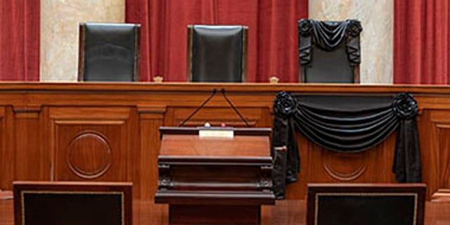 The Courtroom of the Supreme Court showing Associate Justice Ruth Bader Ginsburg's Bench Chair and the Bench in front of her seat draped in black following her death on September 18th, 2020. (Fred Schilling/US Supreme Court)