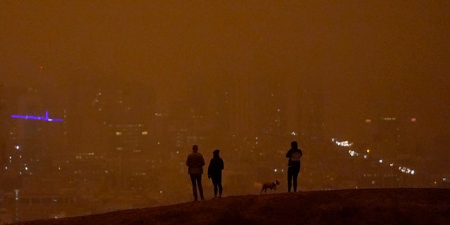 People look toward the skyline obscured by wildfire smoke in daytime from Kite Hill Open Space in San Francisco, Wednesday, Sept. 9, 2020.