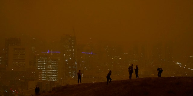 People look toward the skyline obscured by wildfire smoke during daytime from Kite Hill Open Space in San Francisco, Wednesday, Sept. 9, 2020.