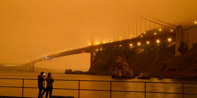 Patrick Kenefick, left, and Dana Williams, both of Mill Valley, Calif., record the darkened Golden Gate Bridge covered with smoke from wildfires Wednesday, Sept. 9, 2020, from a pier at Fort Baker near Sausalito, Calif. The photo was taken at 9:47 a.m. in the morning.