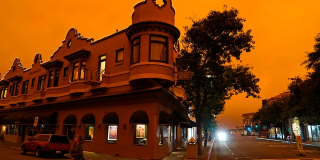 A woman crosses a street by in front of a hotel as smoke from wildfires darken the morning sky Wednesday, Sept. 9, 2020, in Sausalito, Calif.