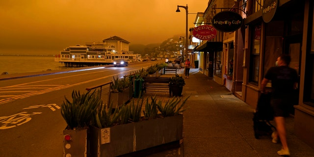 A man walks along Bridgeway Avenue and looks out at the darkened morning sky with smoke from wildfires Wednesday, Sept. 9, 2020, in Sausalito, Calif.