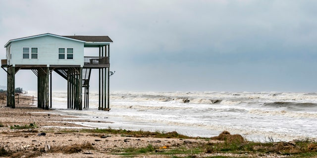 A house sits on the beach on Bolivar Peninsula, Texas, buffeted by the winds and rough surf, Sunday, Sept. 20, 2020.