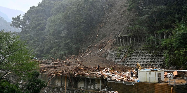 Rescuers work at a mudslide site as Typhoon Haishen hit the mountainous village of Shiiba village, Miyazaki prefecture, southwestern Japan Monday, Sept. 7, 2020.