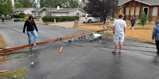 Residents look at a downed power pole that was blown over in high winds on Tuesday, Sept. 8, 2020, in Hyrum, Utah.