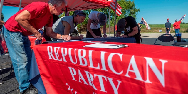 People register to vote during a GOP event in Brownsville, Pennsylvania on September 5, 2020.  Less than two months before the November 3rd presidential election, the contrast between Republicans and Democrats in Washington County is striking in the suburbs of Pittsburgh.  (Photo by ANDREW CABALLERO-REYNOLDS / AFP via Getty Images)