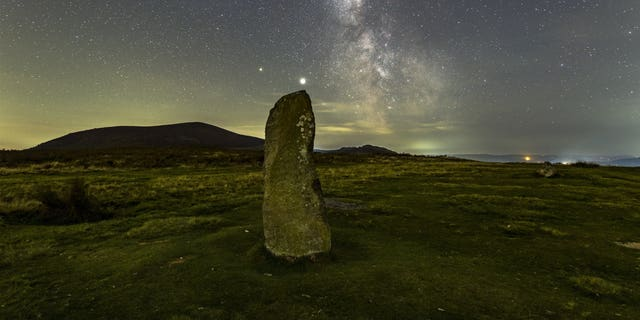 A dramatic night sky aligns with the center stone of the Mitchell's Fold stone circle in southwest Shropshire, September 27, 2020. (Credit: SWNS)