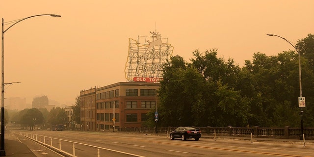 The Portland Oregon Old Town sign is seen under heavy smoke from the wildfires creating an orange glow over Portland, Ore., Saturday, Sept. 12, 2020.