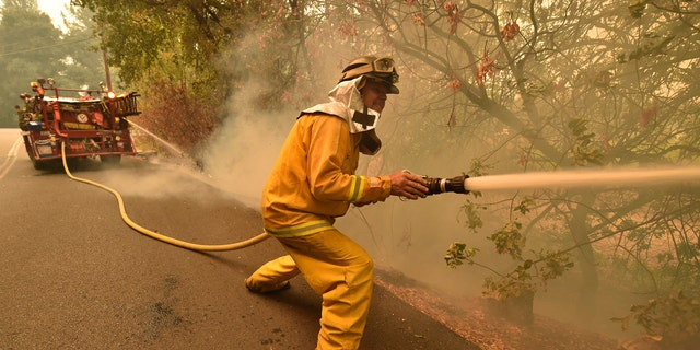 Eagle Field Fire Department firefighter Mark Jones extinguishes hot spots during the Glass Fire in St. Helena, Calif., on Monday, Sept. 28, 2020.