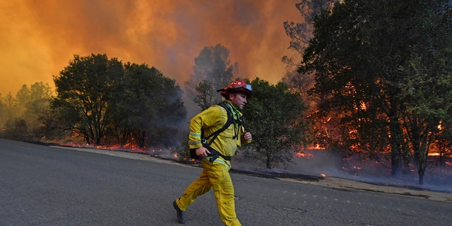 A firefighter runs to his firetruck while protecting a home along Crystal Springs Road while battling the Glass Fire in St. Helena, Calif., on Sunday, Sept. 27, 2020.