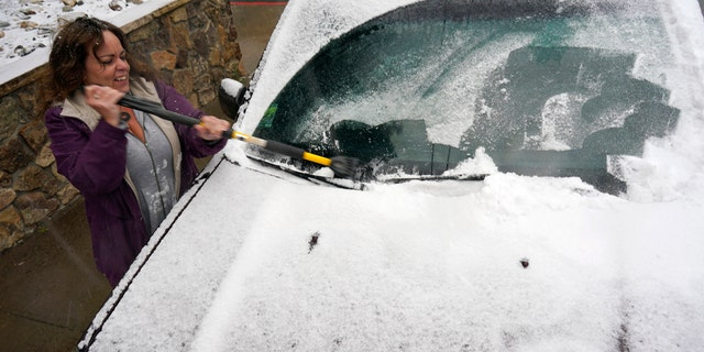Diane Lee cleans the windshield of her sports-utility vehicle as she heads home after a day at her job with the Clear Creek County Sheriff's Department while a storm packing high winds and snow sweeps through the intermountain West Tuesday, Sept. 8, 2020, in Georgetown, Colo.