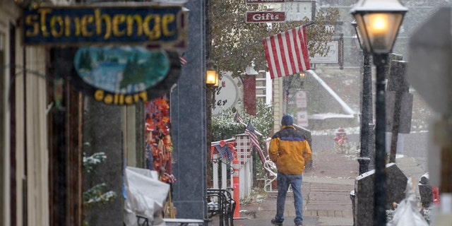 A lone pedestrian moves along the main street as a storm packing high winds and snow sweeps through the intermountain West, Tuesday, Sept. 8, 2020, in Georgetown, Colo.