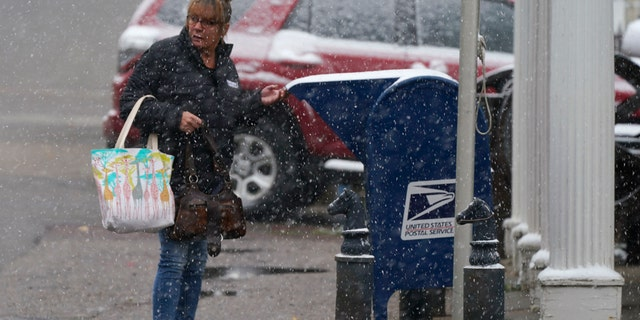 A woman drops off a letter in a mailbox in front of the post office as a storm packing high winds and snow sweeps through the intermountain West Tuesday, Sept. 8, 2020, in Georgetown, Colo.