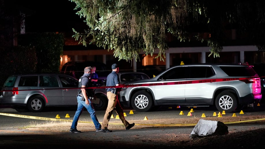 Police walk past evidence markers at a scene Thursday, Sept. 3, in Lacey, Wash., where a man suspected of fatally shooting a supporter of a right-wing group in Portland, Ore., last week was killed as investigators moved in to arrest him. (AP Photo/Ted Warren)