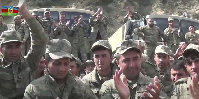 In this grab taken from video released by Azerbaijan's Defense Ministry on Saturday, Oct. 3, 2020, Azerbaijan's solders applaud at a meeting with officers during fighting with forces of the self-proclaimed Republic of Nagorno-Karabakh, Azerbaijan. Armenia and Azerbaijan on Saturday said heavy fighting is continuing in their conflict over the separatist territory of Nagorno-Karabakh. Azerbaijan's president criticized the international mediators who have tried for decades to resolve the dispute. (Azerbaijan's Defense Ministry via AP)